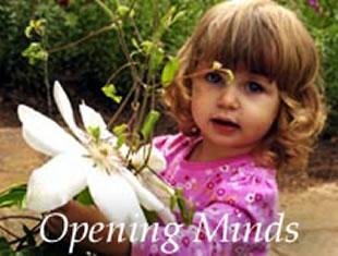 little girl holding flower in garden